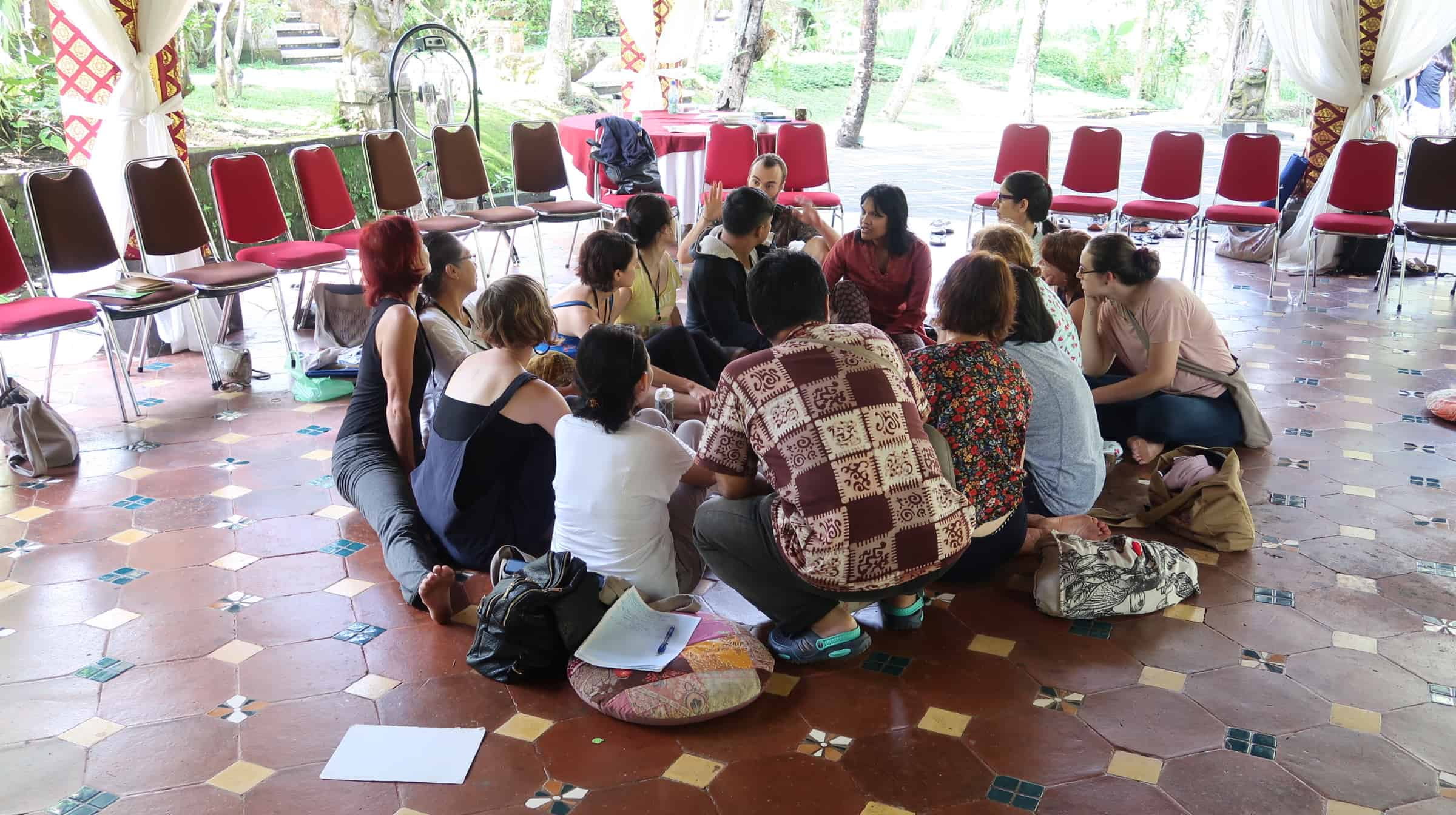 People sitting on floor in circle engaged in an activity.